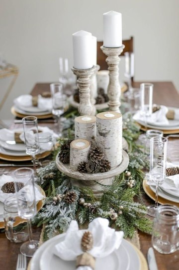 A-snowt-rustic-christmas-table-with-a-flocked-evergreen-runner-pinecones-branch-candleholders-pinecone-napkin-rings