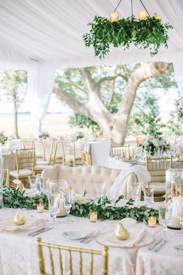 An-elegant-white-spring-wedding-reception-with-greenery-chandeliers-greenery-runners-candles-and-gold-pears