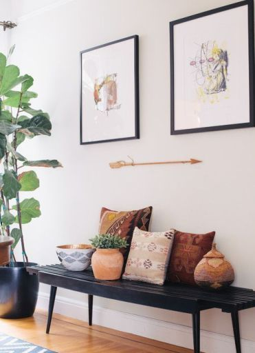 02-a-black-bench-colorful-pillows-potted-plants-artworks-and-an-arrow