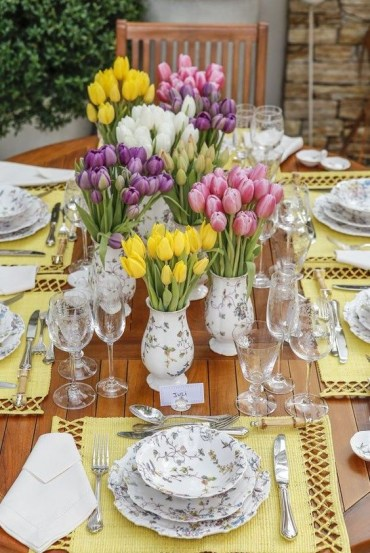 A-colorful-spring-tablescape-with-bright-yellow-placemats-prited-floral-porcelain-and-lots-of-colorful-tulips