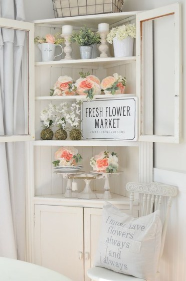 A-corner-bureau-with-fresh-peachy-and-white-blooms-candles-vine-balls-and-an-artwork