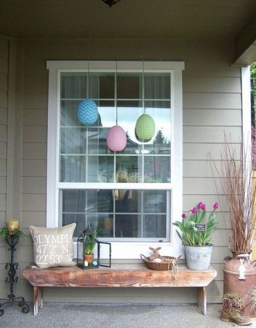 A-cozy-easter-front-porch-with-potted-tulips-colorful-eggs-a-lantern-with-greenery-and-eggs-and-a-bunny