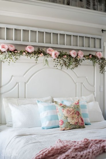 A-floral-pillow-a-pink-blanket-and-a-garland-of-faux-greenery-and-pink-peonies-make-the-bedroom-feel-like-spring