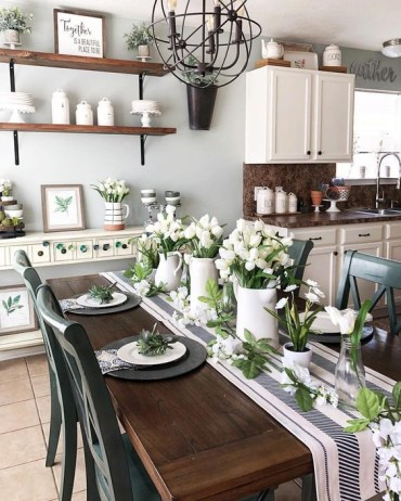 A-fresh-spring-tablescape-with-a-striped-table-runner-black-matte-chargers-white-porcelain-and-white-tulips-centerpieces