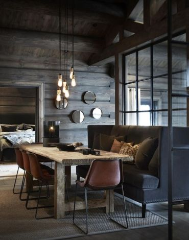 A-moody-chalet-dining-space-with-a-large-black-sofa-pendant-bulbs-a-wooden-table-and-leather-chairs-1