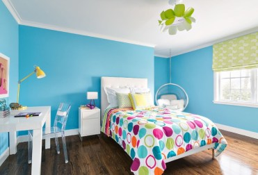 Blue-walls-and-a-white-ceiling-in-a-room-with-dark-brown-laminate-floor-and-a-bed-with-a-colorful-duvet-teenage-girl-room-ideas-white-desk-and-a-clear-plastic-chair