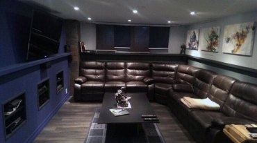 Brown-leather-sectional-with-navy-wall-basement-man-cave