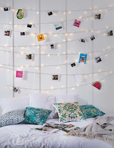 Eight-rows-of-lit-fairy-lights-decorated-with-photos-and-colorful-images-hung-on-a-white-wall-cheap-ways-to-decorate-a-teenage-girls-bedroom