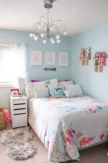 Light-blue-walls-teen-girl-room-decor-colorful-throw-pillows-silver-chandelier-small-wooden-bookshelves-on-the-wall