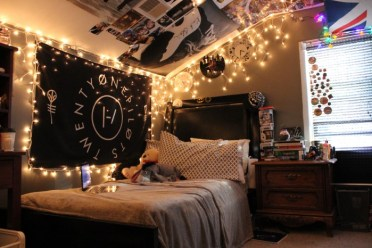 Posters-various-images-and-lit-sting-lights-decorating-the-walls-and-ceiling-of-a-dark-room-teenage-bedroom-ideas-for-small-rooms