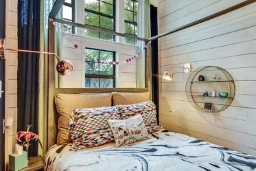 White-wooden-walls-with-small-metal-book-shelf-on-the-wall-colorful-throw-pillows-on-the-bed-tall-windows-teen-girl-room-decor