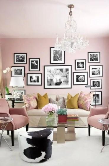 Un-soggiorno-rosa-chic-con-sedie-rosa-chiaro-un-muro-bianco e nero-galleria-e-cuscini-colorati