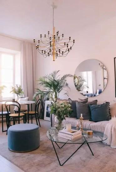 Un-soft-soggiorno-sala da pranzo-con-pareti-arrossate-uno-specchio-rotondo-un-chic-lampadario-tocchi-di-grigio-e-blu marino