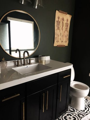 A-stylish-and-moody-bathroom-with-matte-black-walls-a-black-vanity-a-white-stone-countertop-and-catchy-artworks