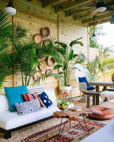 2-22-a-tropical-boho-patio-with-potted-plants-a-white-sofa-boho-rugs-and-an-ottoman-a-living-edge-table-and-decorative-baskets-on-the-wall