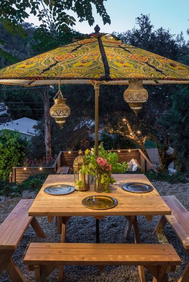 Moroccan-lanterns-and-patterned-umbrella-complete-an-eclectic-outdoor-dining-space