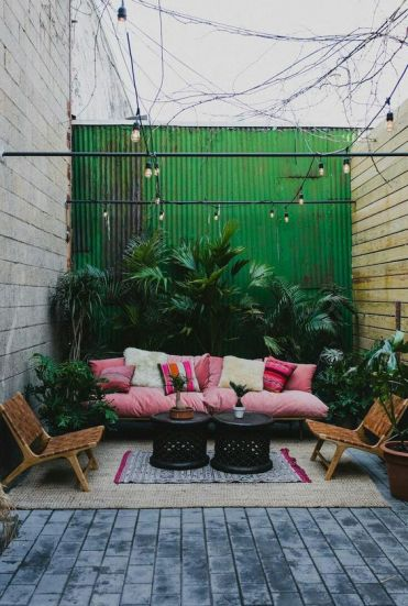 A-bright-tropical-patio-with-a-pink-sofa-and-printed-pillows-leather-chairs-lots-of-lush-plants-in-pots-and-black-tables