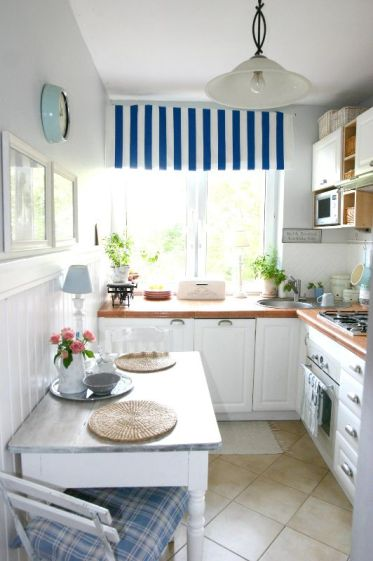 A-cozy-coastal-kitchen-with-white-cabinetry-bold-countertops-striped-and-plaid-textiles-and-a-pendant-lamps