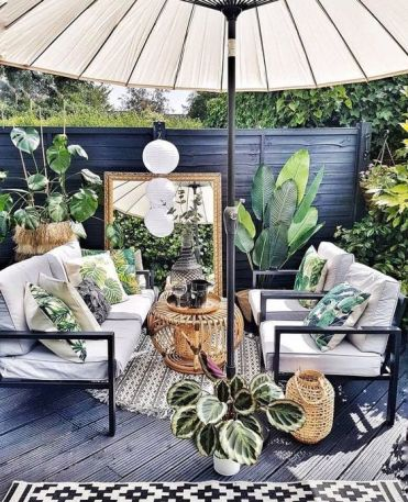 A-small-tropical-patio-done-in-black-and-grey-with-white-furniture-a-large-umbrella-potted-plants-and-tropical-pillows