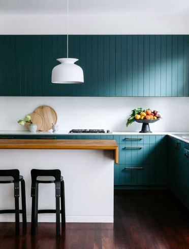 A-stunning-turquoise-coastal-kitchen-with-beadboard-cabinets-a-white-kitchen-island-with-a-stained-countertop-black-stools-and-a-white-pendant-lamp
