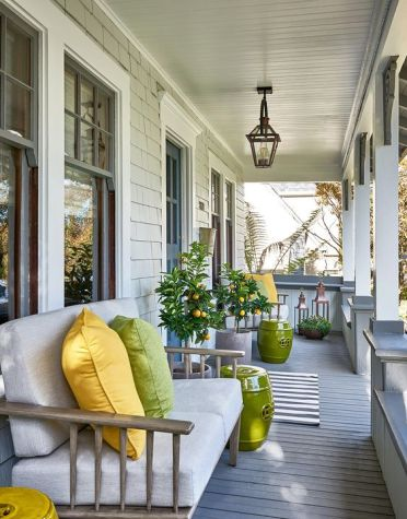 1-a-bright-and-welcoming-summer-porch-with-citrus-trees-a-neutral-loveseat-with-bright-pillows-and-side-tables