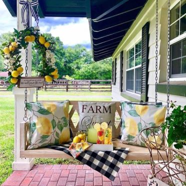 1-a-summer-farmhouse-porch-with-a-hanging-bench-bright-citrus-print-pillows-a-citrus-wreath-and-some-drinks-on-a-tray