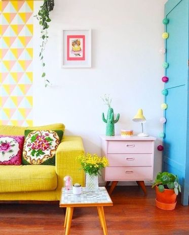 2-a-bright-geometric-hanging-a-yellow-sofa-a-pink-dresser-colorful-garlands-and-blooms-and-greenery-in-pots