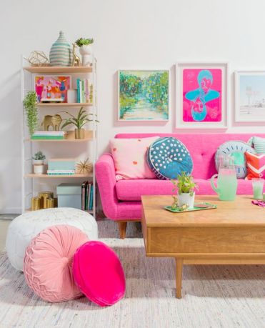 A-bold-living-room-with-colorful-artworks-a-pink-sofa-and-pink-and-blush-pillows-plus-printed-ones