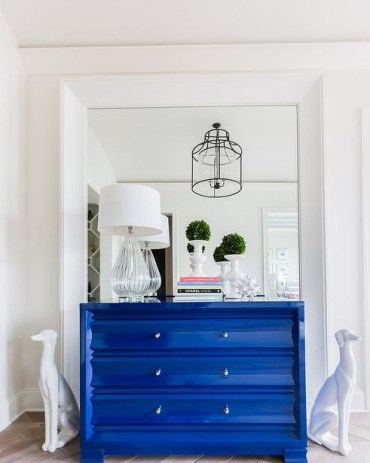 Foyer-mirrored-accent-wall-white-dalmatian-statues-blue-lacquered-chest