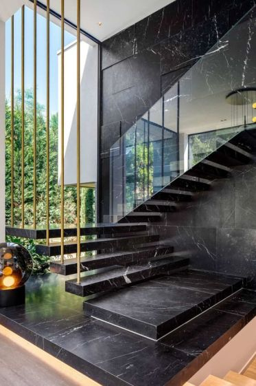 1-19-a-black-marble-wall-and-a-matching-floating-staircase-make-the-layout-luxurious-and-very-chic