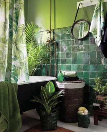 1-a-moody-tropical-bathroom-with-green-walls-and-dark-green-glossy-tiles-a-black-tub-a-woven-stool-potted-plants-and-tropical-print-textiles
