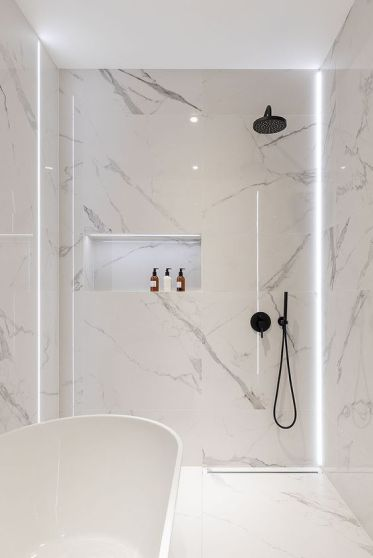 20-a-minimalist-white-bathroom-fully-clad-with-marble-with-a-tub-and-a-shower-plus-built-in-lights-for-a-refined-feel