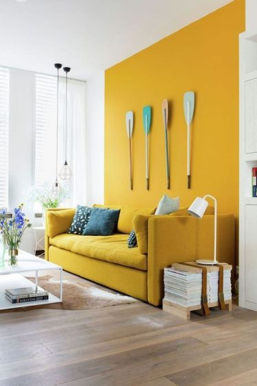 A-bright-modern-living-room-with-a-mustard-accent-wall-and-a-matching-sofa-pendant-lamps-and-oars-on-the-wall