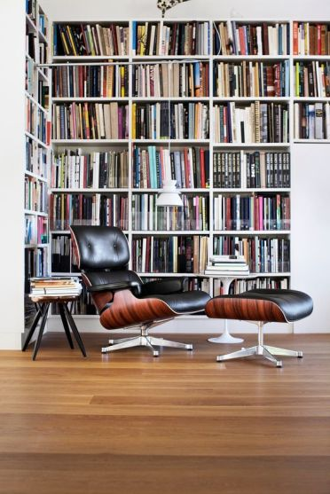A-modern-home-library-nook-with-an-oversized-l-shaped-bookcase-a-black-leather-chair-with-a-footrest