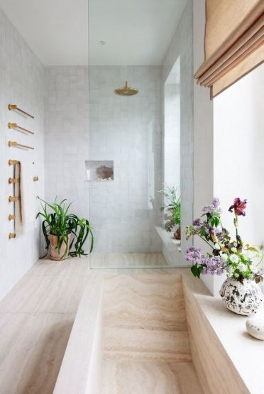 A-neutral-contemporary-bathroom-with-blooms-and-greenery-in-pots-and-touches-of-gold-for-a-chic-and-lively-look