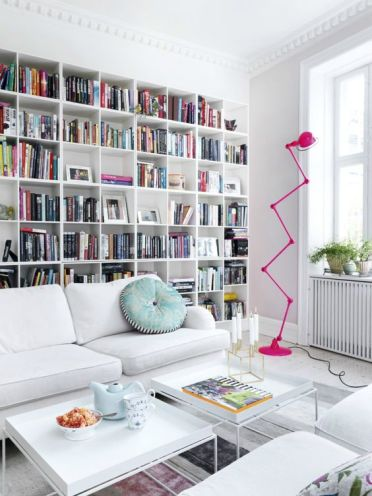 A-stylish-modern-library-with-a-large-built-in-bookcase-white-furniture-and-a-whimsy-hot-pink-floor-lamp