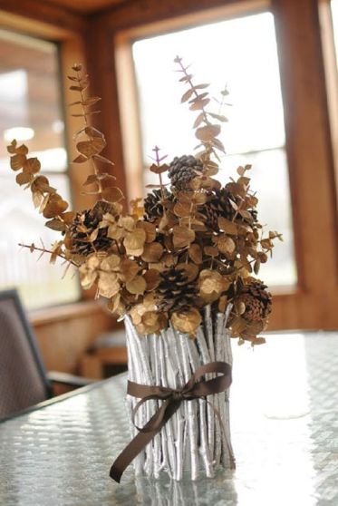 A-vase-covered-with-silver-painted-sticks-and-twigs-dried-eucalyptus-and-pinecones-is-a-chic-fall-centerpiece-1