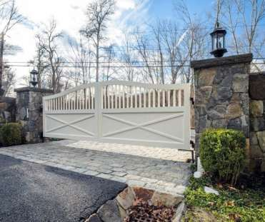 Double-gates-painted-white-for-driveway-entrance-of-home