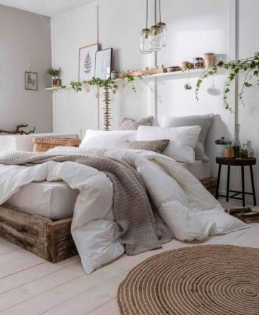 1-a-neutral-boho-bedroom-with-a-rough-wooden-bed-a-jute-rug-an-open-shelf-pendant-lamps-and-greenery