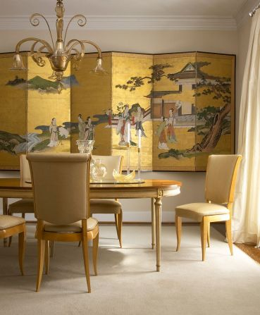 Chinese-decorative-screen-in-gold-creates-a-dramatic-backdrop-for-the-dining-room-in-gold