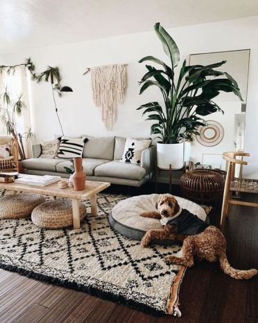 A-bohi-chic-living-room-with-a-printed-rug-and-pillows-a-macrame-hanging-potted-plants-and-jute-ottomans
