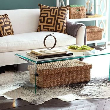 A-clear-glass-table-with-a-large-woven-box-with-a-lid-under-it-it-can-be-used-for-storage-without-cluttering
