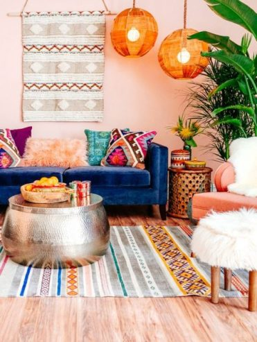 A-colorful-boho-living-room-with-bright-lampshades-pink-walls-boho-rugs-and-pillows-and-a-hammered-metal-coffee-table