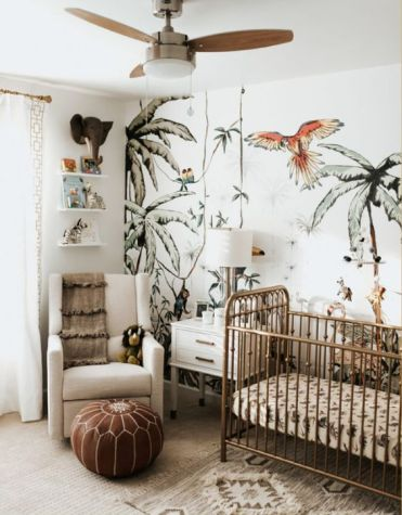 A-jungle-themed-nursery-with-a-fun-printed-wall-tropical-bedding-a-leather-ottoman-cute-jungle-themed-toys