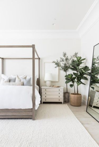 A-neutral-modern-bedroom-with-a-wooden-bed-statement-plants-an-oversized-mirror-and-white-nightstands