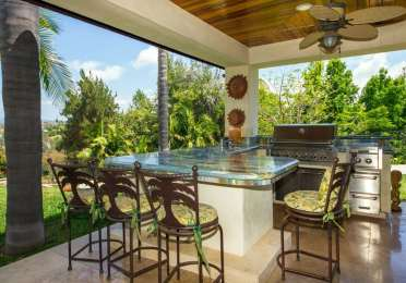 Tropical-outdoor-kitchen-with-granite-counter-peninsula-bar