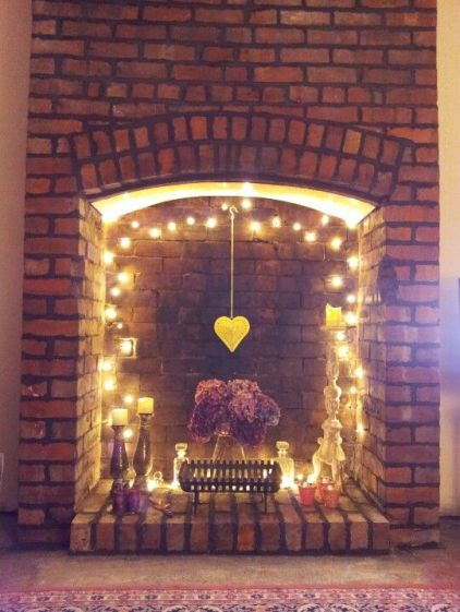 05-a-fireplace-with-string-lights-a-hanging-heart-and-some-candles-for-a-cute-look