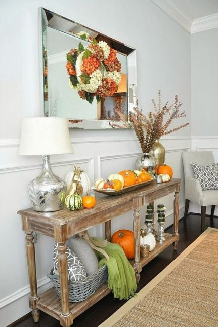 05-a-rustic-console-table-with-pumpkins-on-display-and-a-colorful-fall-wreath-over-it