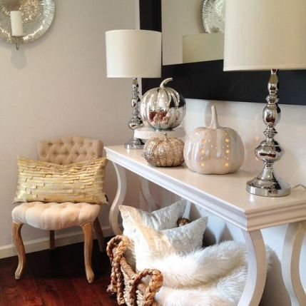 06-a-console-table-with-various-shiny-pumpkins-and-a-wicker-basket-with-pillows-and-faux-fur