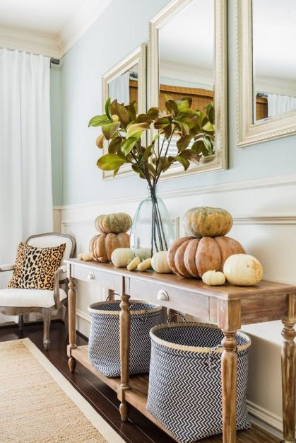 09-a-vintage-farmhouse-console-table-with-chevron-baskets-natural-pumpkins-stacked-on-each-other-and-fall-leaves-in-a-vase